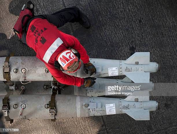 february 20, 2011 - an airman moves ordnance on the flight deck of the aircraft carrier uss carl vinson. - ussカールビンソン号 ストックフォトと画像