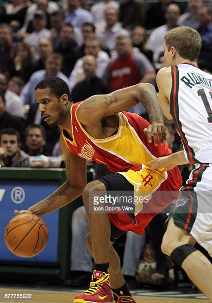 Houston Rockets guard Trevor Ariza drives around Milwaukee Bucks guard Luke Ridnour in the third quarter of a NBA game at the Bradley Center in...