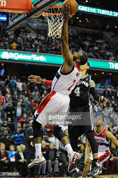 Washington Wizards point guard John Wall scores to send the game into double overtime against San Antonio Spurs shooting guard Danny Green at the...