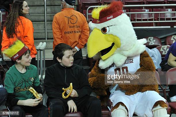 Boston College Eagles mascot Baldwin shares a pretzel with a young fan during the Boston College Eagles game against the North Carolina Tar Heels at...
