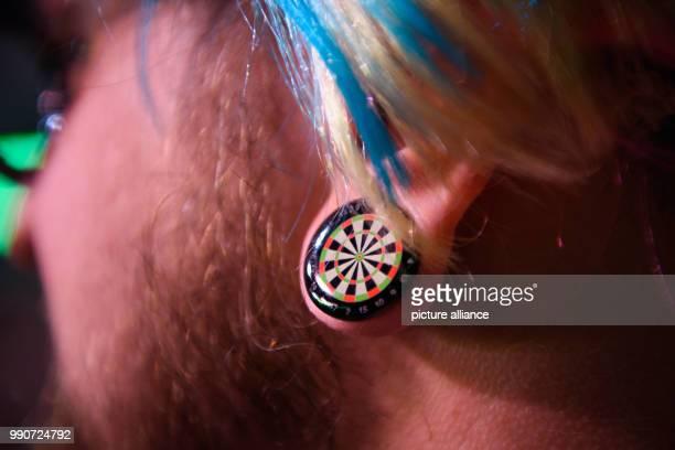 Darts Premier League 4th match day at MercedesBenzArena A fan wears an earring in the shape of a dart board Photo Gregor Fischer/dpa