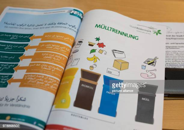The chapter 'Muelltrennung' of Roedermark's welcome brochure is on a table in front of a language guide at the district centre SchillerHaus Language...