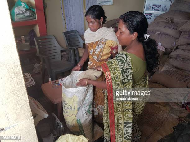 Jolen Minz fills a sack in a hand out office for subsidised rice for her client Rina Devi Many problems occurred during the combination of the hand...