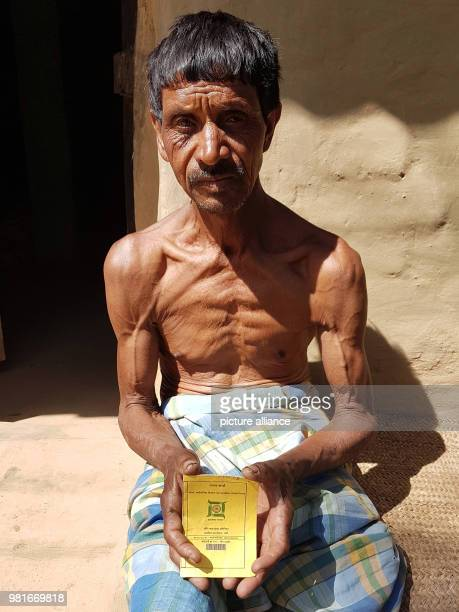 The 62 year old Soma Oraon sits in front of his house and shows his ration card Approximately 86% of the 30 Million inhabitants of the state...
