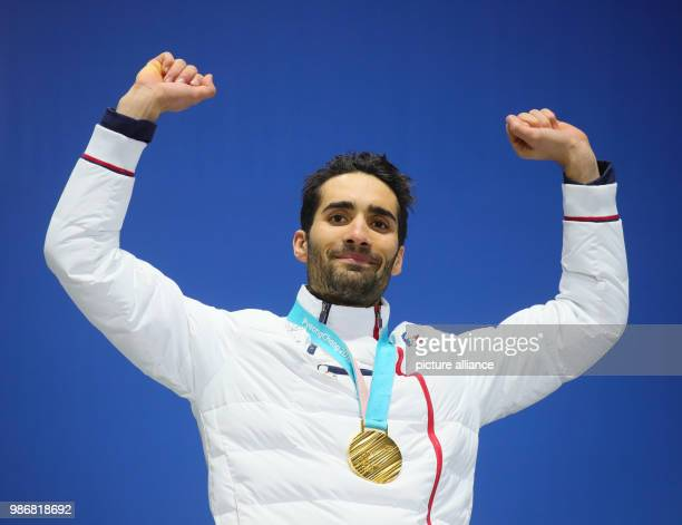 February 2018, South Korea, Pyeongchang: Olympics, Biathlon, Men's Mass Start, Award Ceremony at Medal Plaza: Martin Fourcade from France poses with...