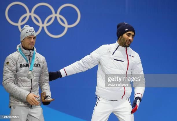February 2018, South Korea, Pyeongchang: Olympics, Biathlon, Men's Mass Start, Award Ceremony at Medal Plaza: Simon Schempp from Germany and Martin...