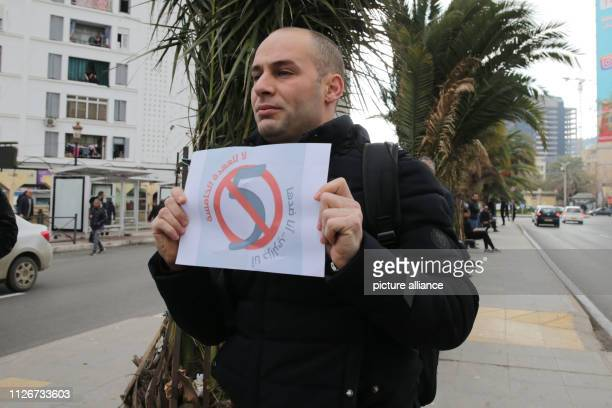 A man holds a note on which the number five is crossed out in protests against the candidacy of Algerian President Bouteflika for a fifth term...
