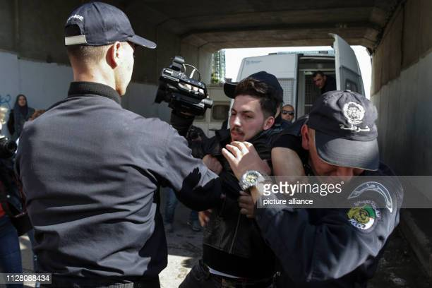 Algerian policemen arrest a man during a protest by journalists against censorship of the press by the authorities as part of the demonstrations...