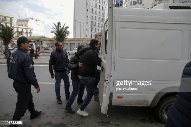 Algerian policemen arrest a protester during a demonstration against the candidacy of Algerian President Abdelaziz Bouteflika for a fifth term in...
