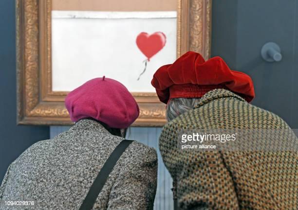 05 February 2019 BadenWuerttemberg BadenBaden Visitors look at the shredded Banksy painting 'Love is in the Bin' in the Frieder Burda Museum The work...