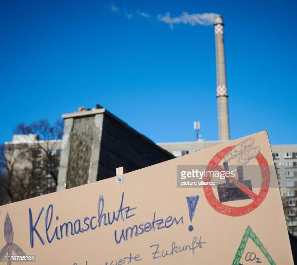 A demonstrator holds a climate protection poster in front of a chimney with smoke In the Invalidenpark a demonstration of pupils for climate...