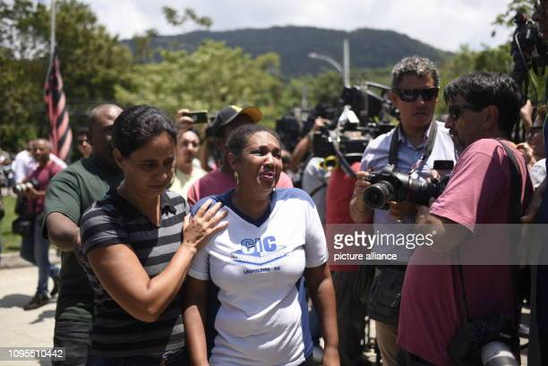 February 2019, Brazil, Rio De Janeiro: Relatives of the victims cry in front of the training centre of the youth team of the Brazilian football club...