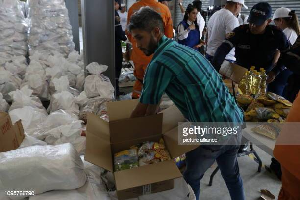 Members of the Colombian fire brigade and helpers organize food that has been stored near the border bridge Tienditas for Venezuela Ten trucks with...