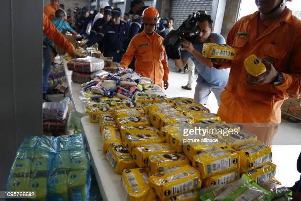 Members of the Colombian fire brigade arrange foods that have been stored near the border bridge Tienditas for Venezuela Ten trucks with around 100...
