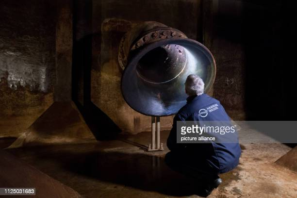 An employee of Hamburg Wasser shines a torch into the pure water inflow in an underground drinking water tank One of Hamburg's largest underground...