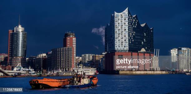 Dark clouds of rain are moving behind the Elbphilharmonie while the front of the concert hall is illuminated by a few sunbeams Photo Axel Heimken/dpa