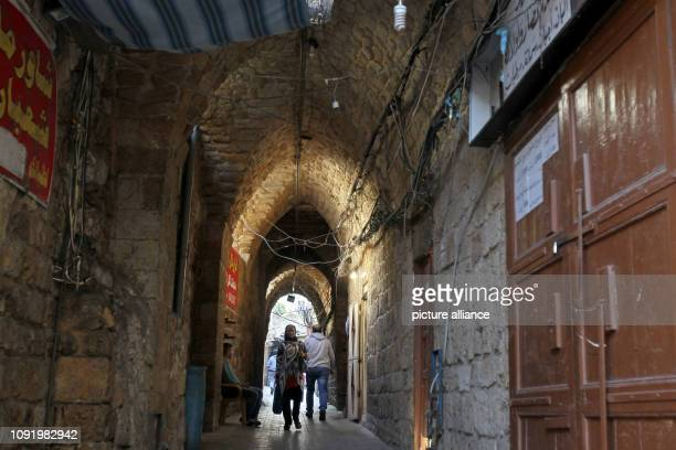 People walk through an alley in the old quarter of the Lebanese port city of Sidon Lebanese Prime Minister Saad alHariri formed a national unity...