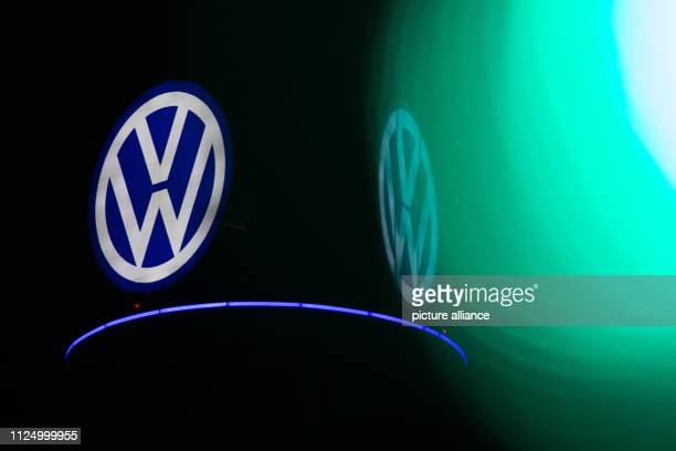 The green light of a traffic light shines in front of the illuminated VW logo on a former television tower in the city centre Photo Raphael...