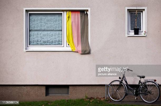 14 February 2019 North RhineWestphalia Herford A German flag hangs in the window of a house with a bicycle in front of it Photo Friso Gentsch/dpa