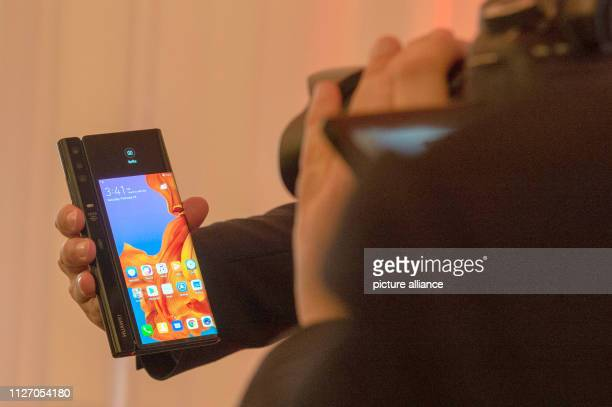 A man shows the back of the folded smartphone Mate X from Huawei with a smaller part of the screen and cameras The Chinese electronics manufacturer...