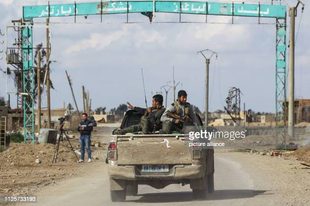 February 2019, Syria, Baghouz: Fighters of the Syrian Democratic Forces , a US-allied Kurdish-led rebel group, patrol through the Islamic State-held...