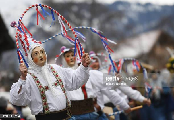 February 2020, Bavaria, Mittenwald: People wear traditional costumes, while the Mittenwald bell stirrers parade through the village during the...
