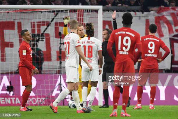 Football Bundesliga Bayern Munich RB Leipzig 21st matchday in the Allianz Arena Referee Marco Fritz gestures next to Thiago Alphonso Davies and...