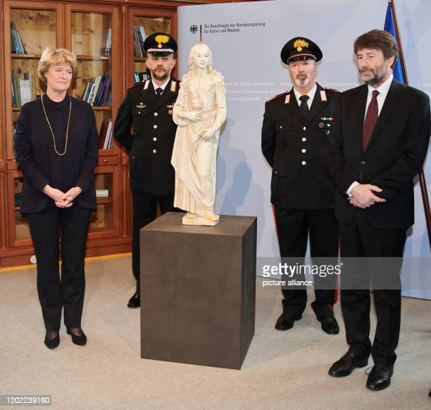 Monika Grütters Minister of Culture and Media and Dario Franceschini Italian Minister of Culture stand next to a guarded statue The statue represents...