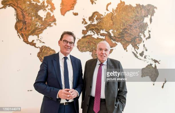 February 2020, Hamburg: Gerd Müller , German Development Minister and Klaus-Michael Kühne, entrepreneur, stand in front of a map of the world at the...