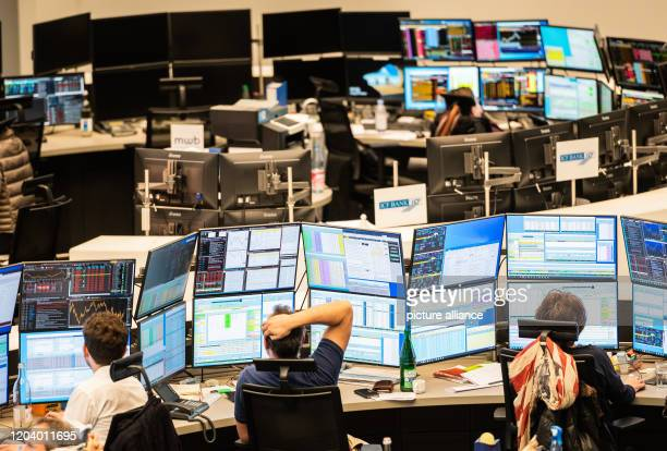 February 2020, Hessen, Frankfurt/Main: Stock traders sit on the trading floor at their workplaces. Germany's leading index, the DAX, is on the...