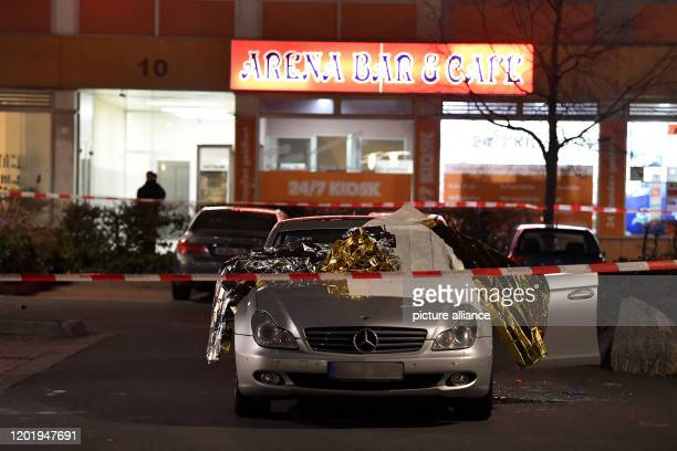 A car is covered with thermo foil next to the car there are glass splinters the crime scene is sealed off with police tape Several people have been...