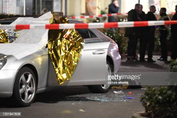 A car is covered with thermo foil next to the car there are glass splinters and a jacket the crime scene is sealed off with police tape Several...