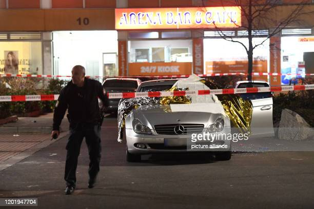 A policeman walks next to a car covered with thermo foil under barrier tape Several people have been killed by gunshots in Hanau Hesse Photo Boris...