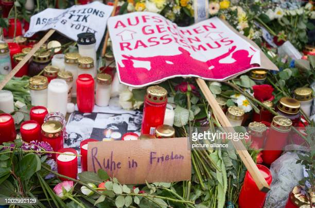 """February 2020, Hessen, Hanau: """"Rest in peace"""" is written on a sign soaked by rain between flowers, candles and other signs at the edge of a Muslim..."""
