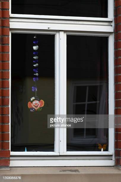 A garland with a clown face hangs in a window The day before a man had driven his car into a carnival parade and injured numerous people including...