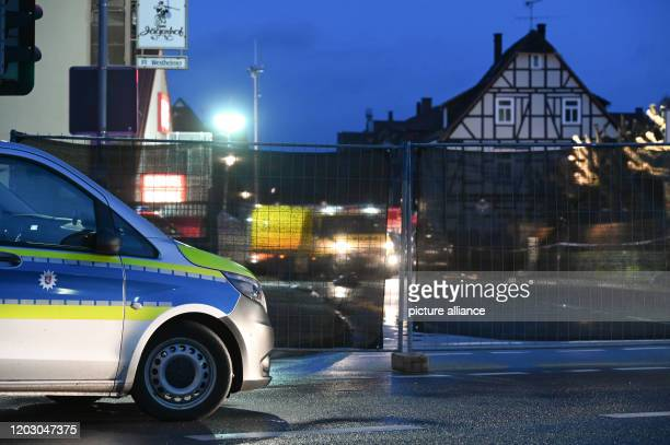 A police car is parked in front of a screen in front of the site where the day before a man raced his car into a carnival parade and injured about 30...