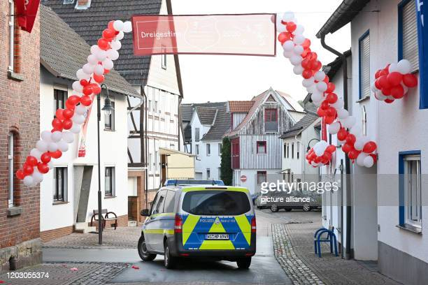 A police car passes under a garland of balloons The day before a man had driven his car into a carnival parade and injured numerous people including...