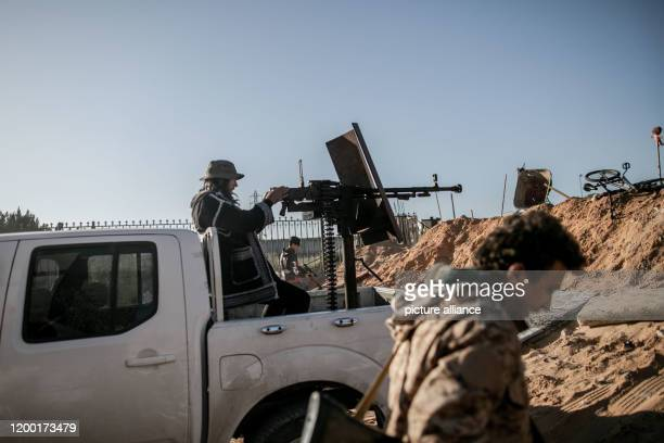February 2020, Libya, Tripoli: A fighter of Libya's UN-backed Government of National Accord of Fayez al-Sarraj, fires a truck-mounted machine gun at...