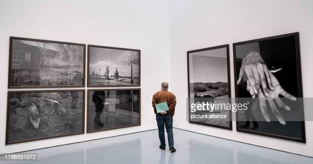 February 2020, North Rhine-Westphalia, Duesseldorf: A visitor stands in front of photos of Peter Lindbergh. Five months after the death of star...