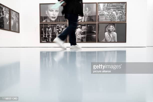 February 2020, North Rhine-Westphalia, Duesseldorf: A visitor walks past photos of Peter Lindbergh. Five months after the death of star photographer...