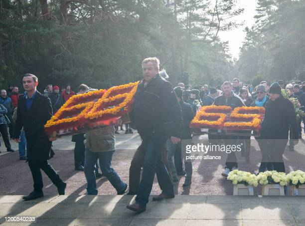 Participants of a commemorative event wear flower arrangements in the form of the numbers 68 and 65 in the Heide Cemetery On the 75th anniversary of...
