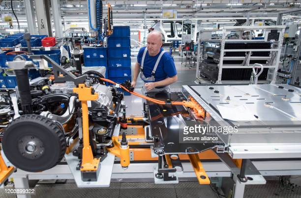 February 2020, Saxony, Zwickau: An employee of Volkswagen Sachsen in Zwickau wires the battery on a line for the new VW ID.3. At the beginning of...