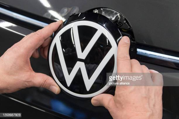 February 2020, Saxony, Zwickau: An employee of Volkswagen Sachsen in Zwickau places the VW logo in the front of the VW ID.3. At the beginning of...