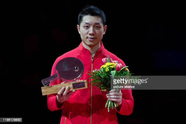 February 2020, Saxony-Anhalt, Magdeburg: Table tennis: German Open, men's, singles, final, Xu - Ma . Winner Xu Xin stands at the award ceremony...