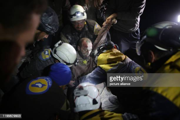 10 February 2020 Syria Abian Sam'an Rescue workers carry a wounded man from a rubble of a building after an airstrike allegedly carried out...