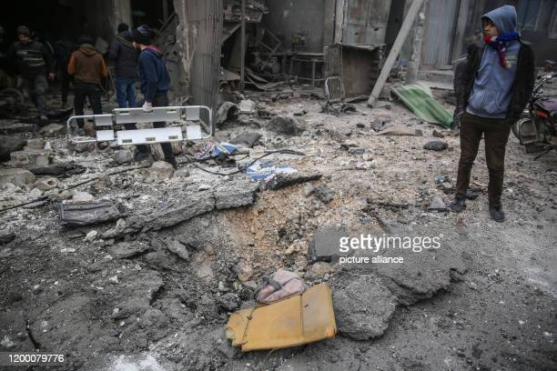 Syrians inspect the damage at a site targeted by multiple airstrikes allegedly carried out bySyrian forces warplanes in the rebelheld Idlib province...