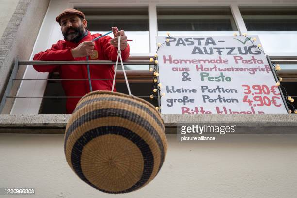"""February 2021, Baden-Wuerttemberg, Tübingen: A restaurateur lowers a basket of pasta from his closed restaurant. With the """"pasta elevator"""" the..."""