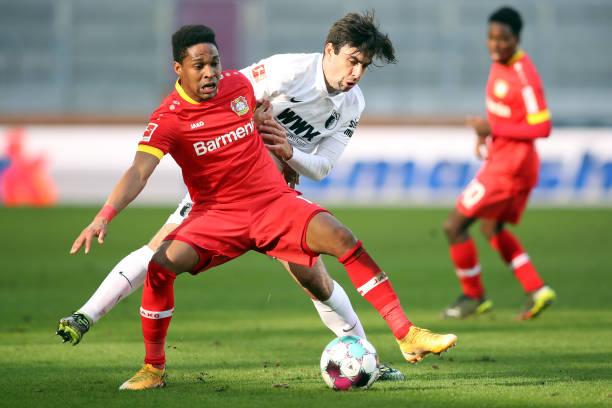February 2021, Bavaria, Augsburg: Football: Bundesliga, FC Augsburg - Bayer Leverkusen, Matchday 22 at WWK Arena. Leverkusen's Wendell and Augsburg's...