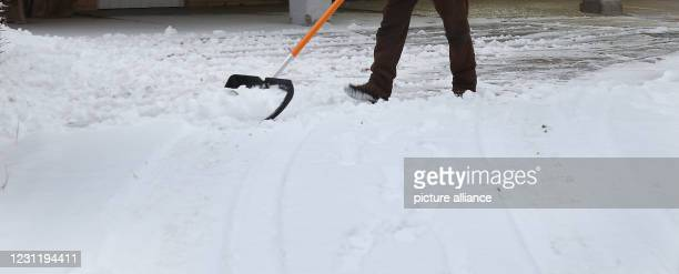 February 2021, Berlin: A man shovels last night's fresh snow out of a driveway in temperatures around minus one degree Celsius. According to...
