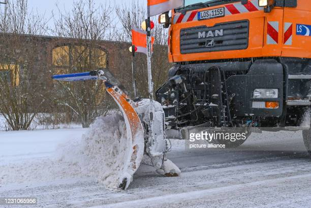 February 2021, Brandenburg, Sieversdorf: A snow plough from the winter road maintenance service is on the move on a village road in the Oder-Spree...
